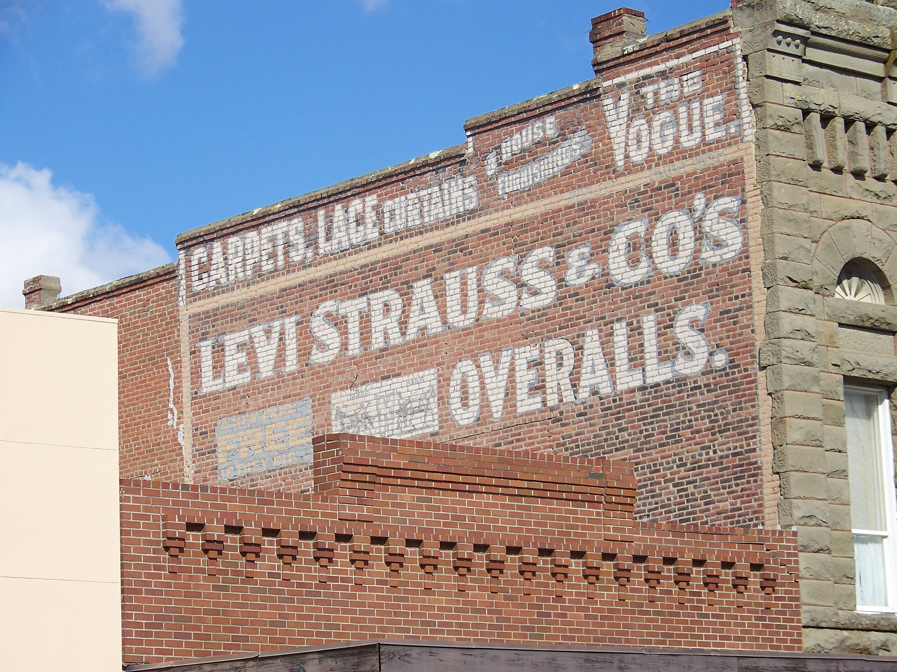 Image of an advertising sign for Levi Strauss & Co. painted on a brick wall; Image credit